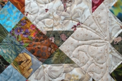 Quilting details shown in the inside of the quilt, around the quilted lambs
